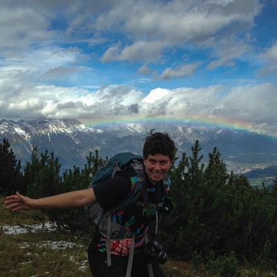 A picture of me in the Alps with a rainbow in the background